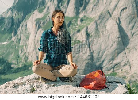 Smiling female hiker sitting in pose of lotos on stone in summer on background of cliffs outdoor
