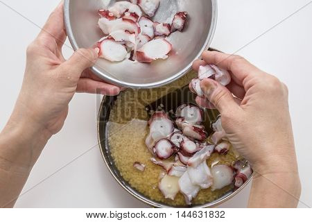 Preparing fresh sliced octopus to cook with rice in the kitchen by hands