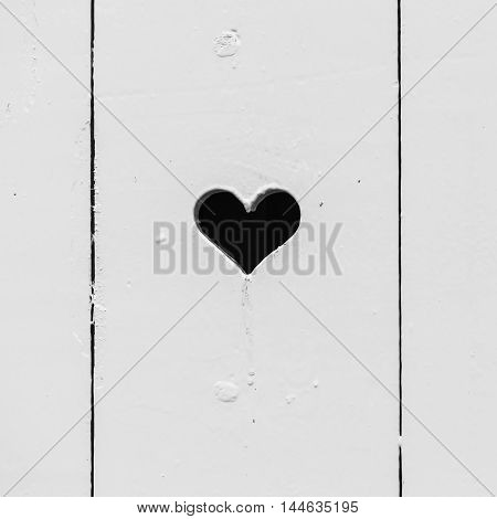 Black heart shaped hole in white wooden wall square background photo texture