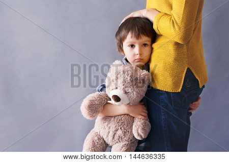 Sad little child boy hugging his mother at home isolated image copy space. Family concept