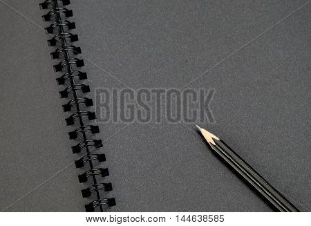 Close Up At Black Pencil On Blank Black Notebook,mock Up For Adding Your Content