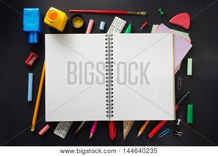 school supplies and notebook on wooden background