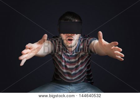 Young man is wearing 3D virtual reality glasses. Low key photo.