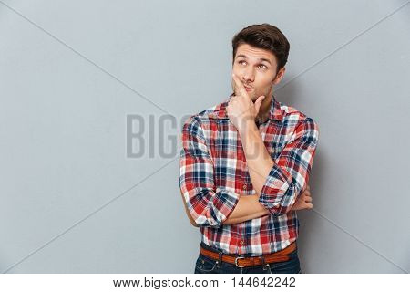Handsome young pensive man standing and looking up isolated on the gray background