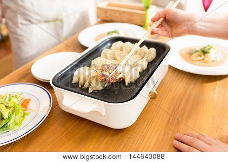 Dumplings baked eyes of crisp on hot black pan in restaurant