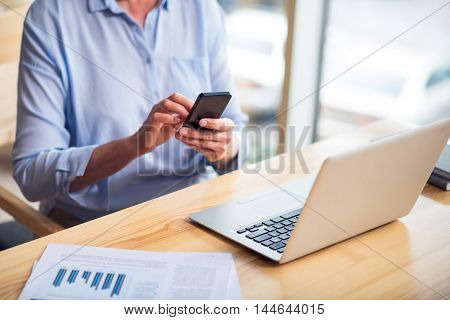 Keep pace of time. Pleasant senior woman using cell phone and sitting at the table
