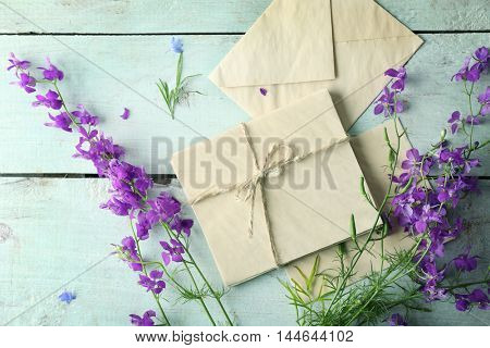 Paper envelopes and delphinium flowers on wooden background, top view