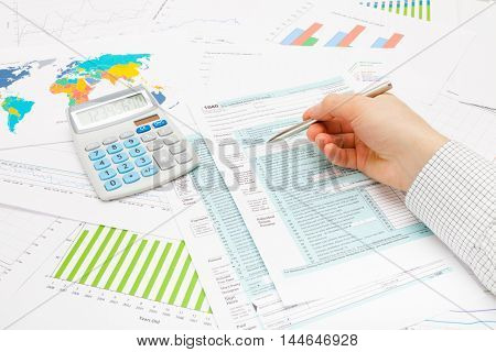 Studio Shot Of A Business Man Pointing With Ball Pen On 1040 Us Tax Form