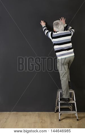 Professor man of university or colleage using ladder for proving theory in studio. Teacher explaining material to students or pupils.