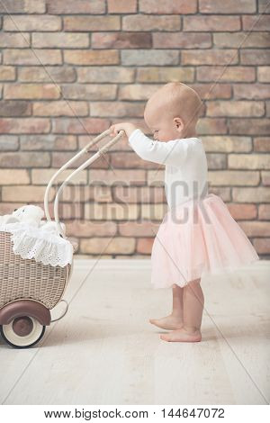 Baby girl playing with toy baby carriage