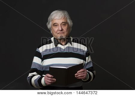 Picture of professor man of university or colleage smiling for camera. Handsome academic holding notebook in studio.