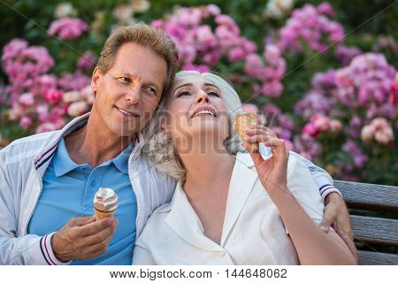 Man smiles and hugs woman. Couple with ice cream. Let's have a rest together. Every moment is priceless.