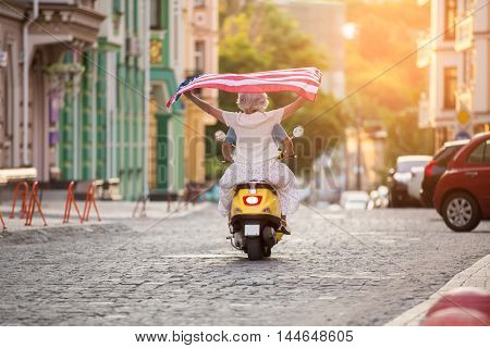 Couple rides yellow scooter. Mature woman holds american flag. Freedom and love. Road to the sun.