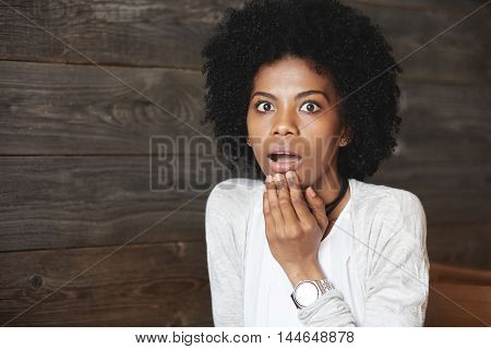 Human emotions and feelings. Close-up portrait of suprised African American female student with Afro haircut shocked with results of exams touching her chin and screaming looking puzzled and scared poster