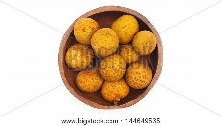 Longan in wood bowl macro photo top view select focus at longan center on white wood.