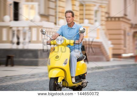 Adult man rides yellow scooter. Scooter on the empty road. Good fuel accelerates engine. Compact mean of transport.