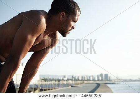 Portrait Of Fit Male Jogger Relaxing After Cardio Running Workout At Seaside. Handsome Athlete With