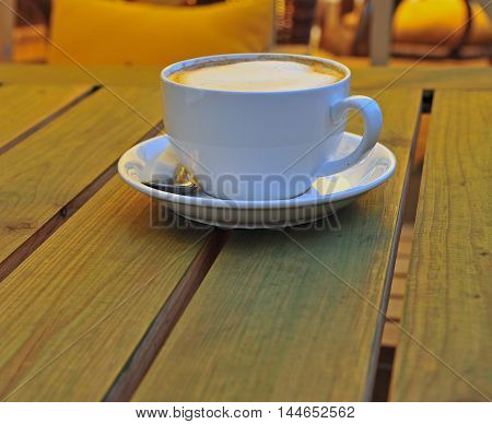 Cup of cappucino on the wooden table