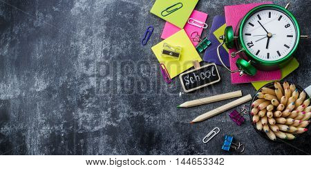 Education, back to school concept. School stationery, supplies, pencil, pen, note, alarm clock on a grunge chalkboard. Selective focus, flat lay top view copy space background