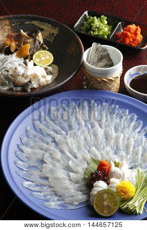 Wakasa blowfish or fugu thin fillet in big platter with lemon sauce wasabi and herbs