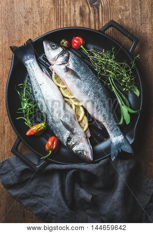 Raw uncooked seabass fish with lemon slices, herbs and spices on black grilling iron pan over rustic wooden background, top view, vertical composition