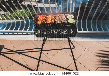 Delicious Meat On Barbecue Grill With Coal On Balcony.