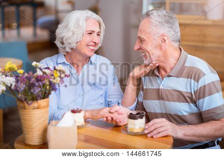 Sincere relations. Cheerful delighted senior couple expressing love and sitting at the table while resting in the cafe