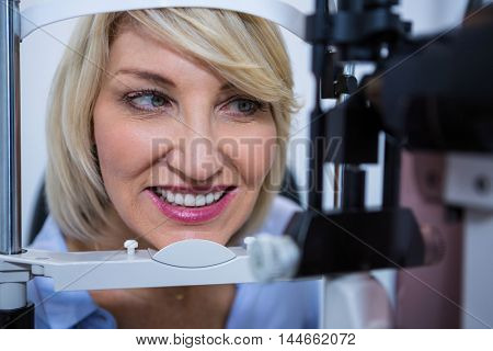 Female patient under going eye test on slit lamp in ophthalmology clinic