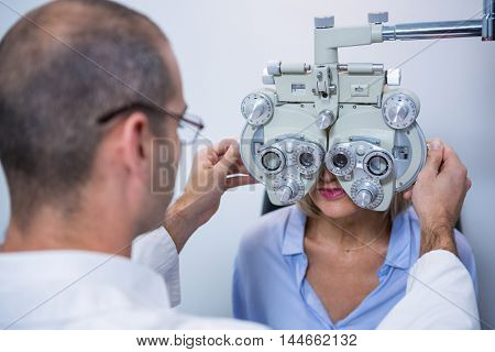 Optometrist examining female patient on phoropter in ophthalmology clinic