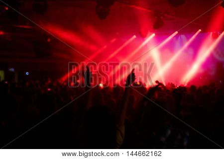 Large crowd of cheering excited fans dancing and jumping in front of big stage in rays of red light
