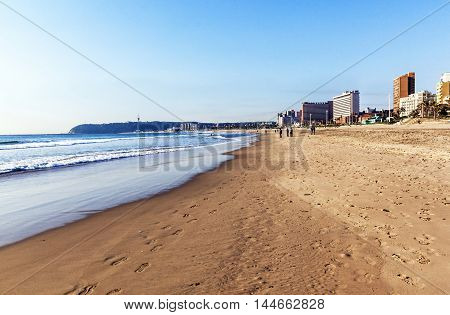 DURBAN SOUTH AFRICA - AUGUST 25 2016: Early Morning unknown people on quiet beach against city skyline and the Bluff in Durban South Africa