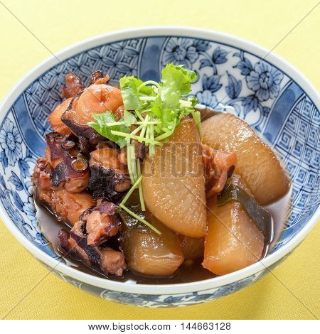 Sauteed octopus with white radish and cumin herbs in traditional Japanese bowl
