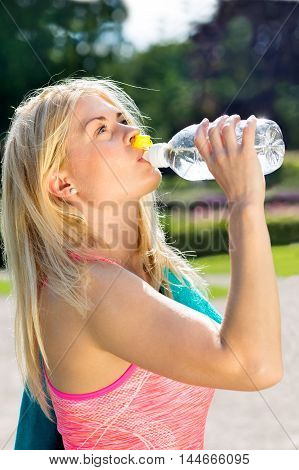 Close up of single thirsty fit frizzy haired blond woman with towel around neck gulping water from bottle after a long run poster