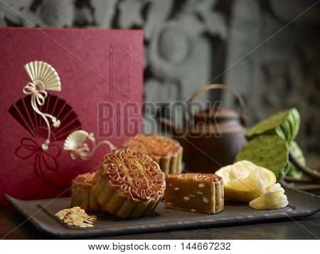 Oriental mooncake with silver lotus paste yuzu and melon seeds on black platter with tea pot