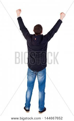 Back view of man. Raised his fist up in victory sign. Rear view people collection. guy in a black jacket raised his hands clenched into fists, hands up.