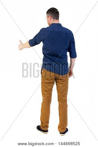 Back view of business man shows thumbs up. man in a blue shirt with the sleeves rolled up showing the right hand thumb up.
