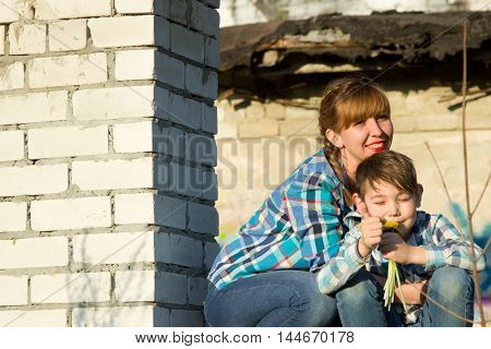 Mom and son in an abandoned building sitting on the window