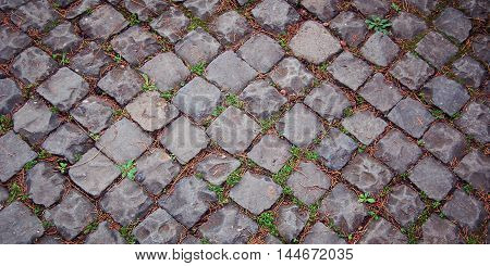 Old pavement. Stone roadway with grass. Ancient pavement in Rome. Vintage effect photo. Wide format. Roman stone pavement with grass growing through. Italy.
