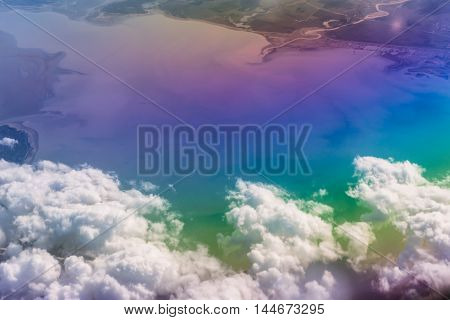 Airplane flying cumulus clouds over Black sea and Caucasus mountains. View of sky from aircraft long distance travel by airtransport. Russia, Krasnodar Krai