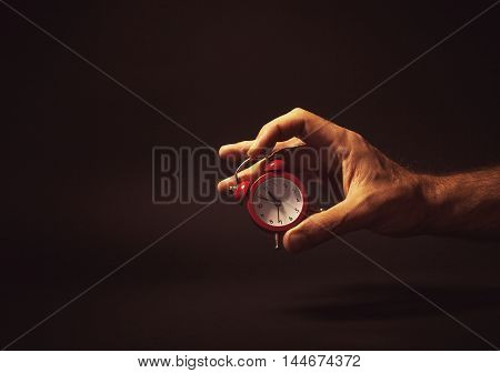 Male Hand Holding A Red Clock