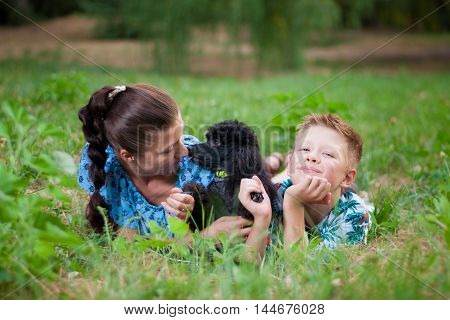 mother with son and a black poodle funny lie on green grass