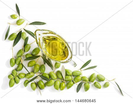 Top view of angular frame of green fresh olives with leaves and olive oil in a glass sauceboat isolated on white background.