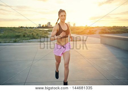 Attractive fit woman enjoying a morning workout jogging along a rural road and forecourt at sunrise approaching the camera front on