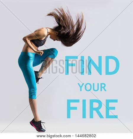 Beautiful young fit modern dancer lady in blue sportswear warming up working out dancing with her long hair flying full length studio image on gray background. Motivational phrase