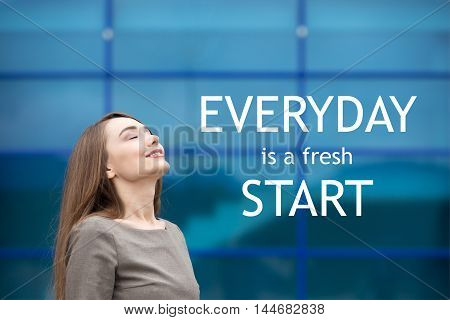 Portrait of cheerful young woman relaxing outdoors with closed eyes. Happy beautiful successful female breathing fresh air on the street in summer. Motivational text