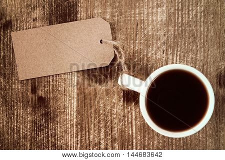 Coffee cup with paper blank tag on wooden background