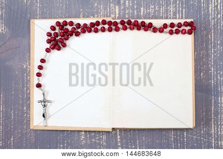 Open book and catholic rosary on wooden background