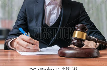 Lawyer is writing and gavel in front. Justice and Law concept.