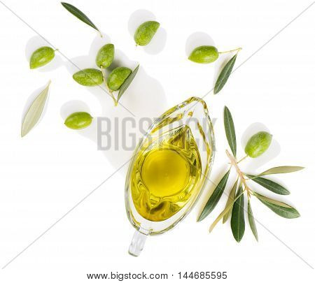 Top view of sauceboat with olive oil and fresh green olives isolated on white background.