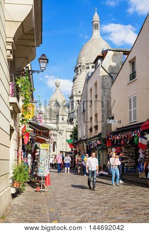Paris France - July 06 2016: The charming shopping street of Montmartre hill near basilica Sacre Coeur with tourists and parisians. The quarter is full of art galleries and cafes. It's one of the most visited landmarks in Paris